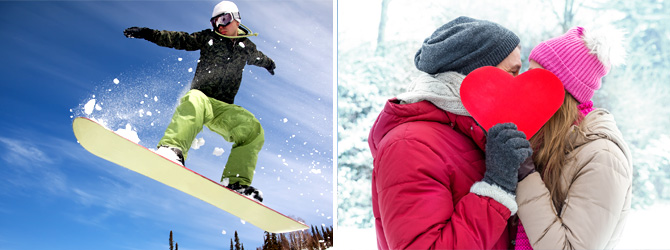 Snow boarder getting air and couple kissing behind a cardboard heart in snow