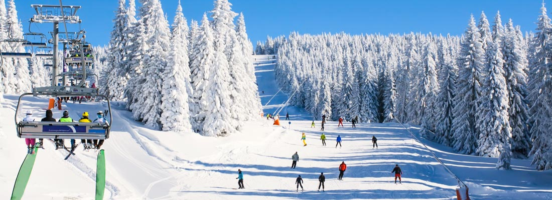 snow covered mountain, ski lift and skiers
