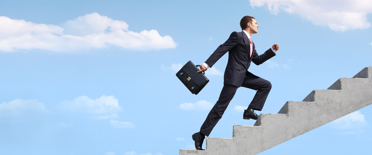 Man in a suit with a briefcase, climbing stairs.